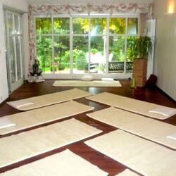 Yoga Augsburg: Heller Yoga-Raum mit 12 Yoga-Matten aus Schurwolle und Blick in den Garten